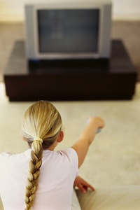 rear view of a girl pointing remote to a television