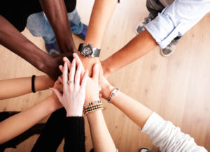 People putting their hands in; ready to work together.