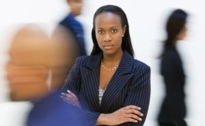 African-American businesswoman standing with arms crossed while others walk by.