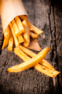 Selective focus on the front french fries on wooden table
