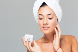 Woman with towel on head holding cream jar