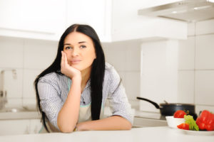 Beautiful woman thinking in kitchen