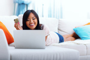 Happy asian woman shopping on-line while lying on the sofa