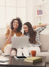 Two excited women shopping online with credit card and laptop sitting on sofa at home, copy space