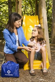 Hispanic girl sitting on playground slide while woman applies first aid bandage to knee.
