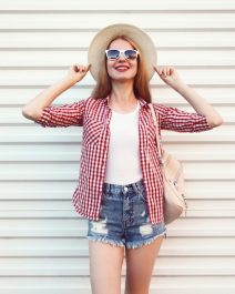 Happy smiling young woman posing in summer round straw hat, checkered shirt, shorts on white wall background