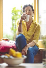 Mature woman is having the morning coffee at home