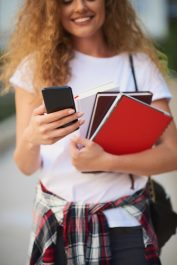 Female student using smart phone and holding books while walking in campus.
