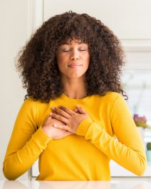 African american woman wearing yellow sweater at kitchen smiling with hands on chest with closed eyes and grateful gesture on face. Health concept.