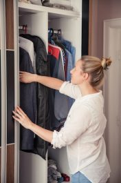 Caucasian woman is reaching for clothes from her closet.