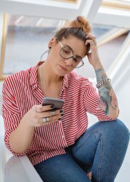 Lovely woman with eyeglasses in red and white shirt, sitting in the kitchen during breakfast using her phone.