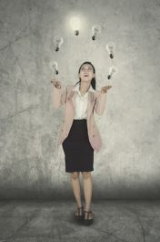 Full length of female entrepreneur juggling with light bulbs while standing with happy expression