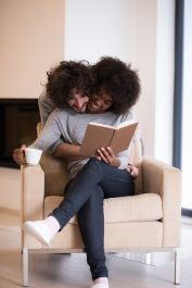 Young beautiful multiethnic couple hugging in front of fireplace at home when reading a book at autumn day
